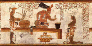 A possible Maya lord forbids a person to touch a container of chocolate.